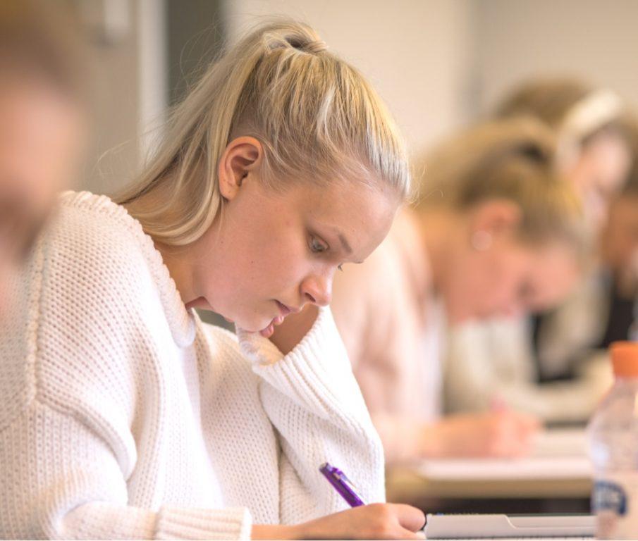 Nuori nainen opiskelee keskittyneesti pöydän ääressä