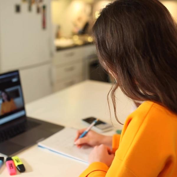 Tummahiuksinen naisopiskelija tekee muistiinpanoja paperille ja katsoo videota kannettavalta tietokoneelta.